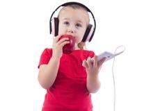 Kleines Mädchen mit einem Apfel und Kopfhörern eines Telefons Lizenzfreie Stockbilder