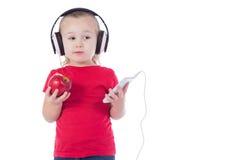 Kleines Mädchen mit einem Apfel und Kopfhörern eines Telefons Lizenzfreie Stockfotos