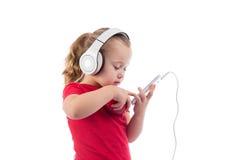 Kleines Mädchen mit einem Apfel und Kopfhörern eines Telefons Lizenzfreies Stockbild