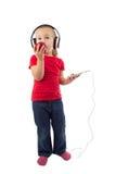 Kleines Mädchen mit einem Apfel und Kopfhörern eines Telefons Stockbild
