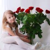 Kleines Mädchen mit einem Bündel roten Rosen Stockbilder