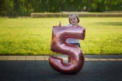Kleines Mädchen mit einem Ballon in Form einer Tabelle fünf Ein Minimann, der ein Bündel Ballone anhält, steht auf einem Kalender Lizenzfreie Stockbilder