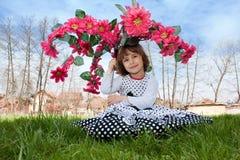 Kleines Mädchen mit einem Blumenregenschirm Stockfotos