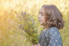 Kleines Mädchen mit einem Blumenstrauß von wilden Blumen, Porträt stockfotografie