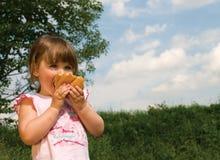 Kleines Mädchen mit einem Brot Stockbild