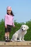 Kleines Mädchen mit einem goldenen Apportierhund Lizenzfreies Stockfoto