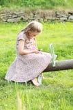 Kleines Mädchen mit einem Handy auf einem Schwingen Lizenzfreie Stockbilder