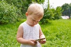 Kleines Mädchen mit einem Handy im Freien Lizenzfreie Stockbilder
