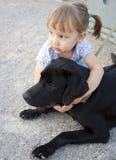 Kleines Mädchen mit einem Hund draußen Lizenzfreies Stockbild