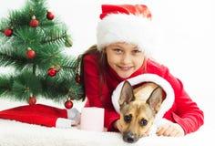 kleines Mädchen mit einem Hund kleidete in den Weihnachtskostümen an Stockbild