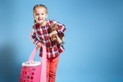 Kleines Mädchen mit einem Koffer und einem Lieblingsspielzeug auf einem blauen Hintergrund kleines Auto auf Dublin-Stadtkarte lizenzfreie stockfotografie
