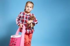 Kleines Mädchen mit einem Koffer und einem Lieblingsspielzeug auf einem blauen Hintergrund kleines Auto auf Dublin-Stadtkarte stockfoto