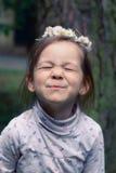 Kleines Mädchen mit einem Kranz von Gänseblümchen auf ihrem Kopf Stockfotografie