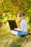Kleines Mädchen mit einem Laptop im Park Lizenzfreies Stockbild