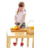 Kleines Mädchen mit einem Messer schneidet Gemüse Lizenzfreie Stockbilder