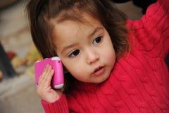 Kleines Mädchen mit einem Mobiltelefon Stockfotos