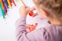 Kleines Mädchen mit einem Pinsel und Lacken stockbild