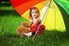 Kleines Mädchen mit einem Regenbogenregenschirm im Park Stockfotos