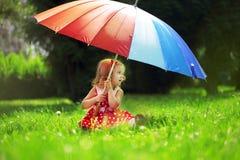 Kleines Mädchen mit einem Regenbogenregenschirm im Park Stockbild