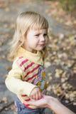 Kleines Mädchen mit einem sauren Gesicht, das Süßigkeit von den Händen der Mutter nimmt. Lizenzfreie Stockbilder