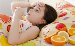Kleines Mädchen mit einem Thermometer im Bett lizenzfreie stockfotos