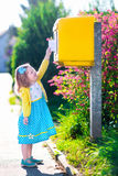 Kleines Mädchen mit einem Umschlag nahe bei einem Briefkasten Stockfotografie