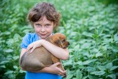 Kleines Mädchen mit einem Welpen in ihren Armen Stockfotos