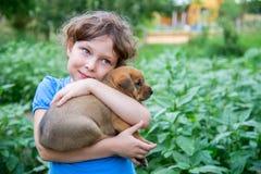 Kleines Mädchen mit einem Welpen in ihren Armen Lizenzfreies Stockbild