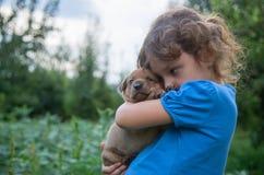 Kleines Mädchen mit einem Welpen in ihren Armen Stockfoto