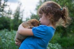 Kleines Mädchen mit einem Welpen in ihren Armen Stockbild