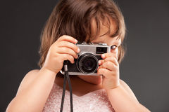 Kleines Mädchen mit einer alten Kamera stockfotografie