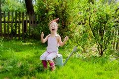 Kleines Mädchen mit einer Gießkanne im Garten Stockbilder