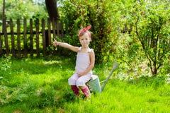 Kleines Mädchen mit einer Gießkanne im Garten Lizenzfreies Stockbild