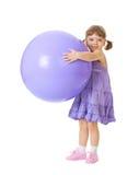 Kleines Mädchen mit einer großen purpurroten Kugel Lizenzfreies Stockbild