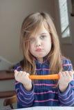 Kleines Mädchen mit einer Karotte Stockbild