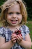 Kleines Mädchen mit einer Kirsche in ihren Händen Lizenzfreies Stockfoto