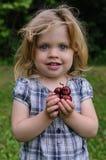 Kleines Mädchen mit einer Kirsche in ihren Händen Lizenzfreies Stockbild