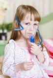 Kleines Mädchen mit einer Maske für Einatmungen Lizenzfreies Stockfoto