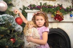 Kleines Mädchen mit einer Puppe in den Händen. Stockbild