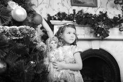 Kleines Mädchen mit einer Puppe in den Händen. Lizenzfreies Stockbild