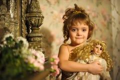 Kleines Mädchen mit einer Puppe in den Händen. Stockfoto