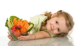 Kleines Mädchen mit einer Schüssel Gemüse Stockfotos
