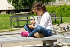 Kleines Mädchen mit einer Tablette in den Händen draußen, den Tablettenschirm aufmerksam betrachtend Lizenzfreies Stockfoto