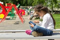 Kleines Mädchen mit einer Tablette in den Händen, den Tablettenschirm aufmerksam betrachtend Stockfoto