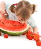Kleines Mädchen mit Erdbeere und Wassermelone Stockfotos