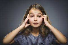 Kleines Mädchen mit erstauntem Ausdruck bei der Stellung gegen grauen Hintergrund Stockbilder