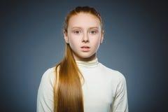 Kleines Mädchen mit erstauntem Ausdruck bei der Stellung gegen grauen Hintergrund Lizenzfreies Stockfoto