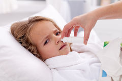 Kleines Mädchen mit falscher Kälte unter Verwendung des nasalen Sprays Lizenzfreie Stockfotografie