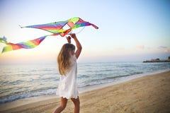 Kleines Mädchen mit Fliegendrachen auf tropischem Strand bei Sonnenuntergang Stockbild