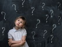 Kleines Mädchen mit Fragezeichen auf Tafel Konzept für Verwirrung, Brainstorming und Wahl stockfoto
